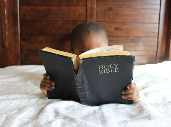 Child sitting on a bed reading the Bible