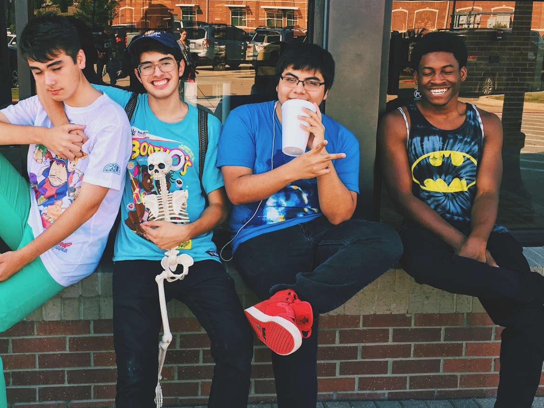 Four teenage boys sitting side-by-side