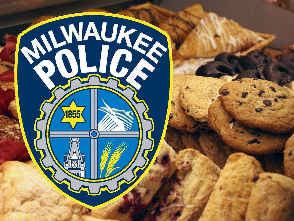 Milwaukee Police badge in front of platters of assorted cookies