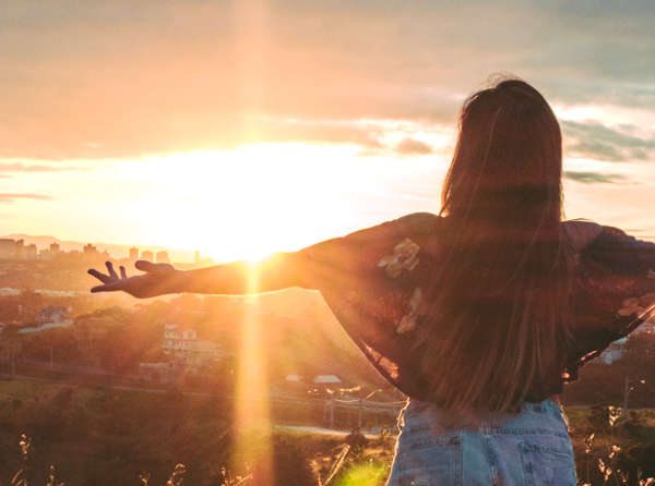 Woman with arms outstretched towards a sunset